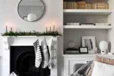 12 a minimalist Christmas mantel with a fresh greenery runner, grey candles, grey and white stockings and house candleholders