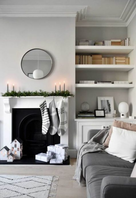 a minimalist Christmas mantel with a fresh greenery runner, grey candles, grey and white stockings and house candleholders