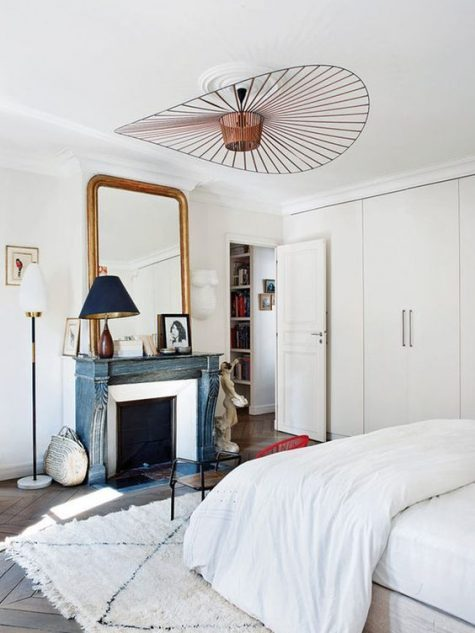 a neutral Parisian bedroom with a blue non working fireplace, a statement lamp, a chic mirror and an antique wooden chair