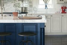 12 a white farmhouse kitchen with a metallic navy kitchen island and matching marble countertops everywhere