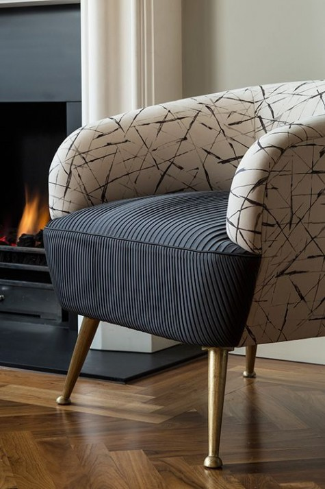 a chic chair with a rounded back with an abstract print and a black draped seat plus gilded legs looks modern and very chic
