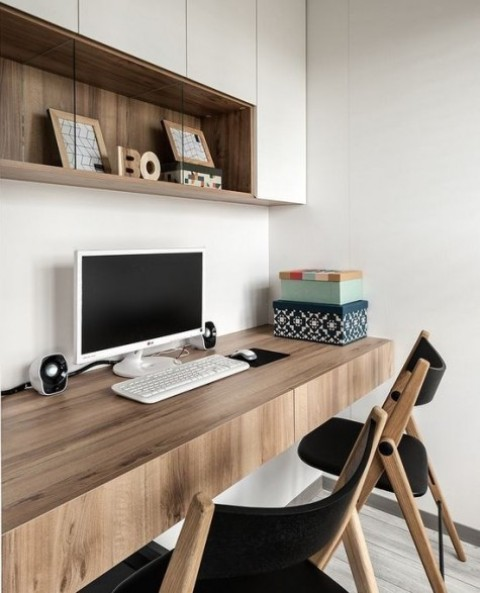 a contemporary home office with a closed storage unit, a floating desk with drawers and a couple of chairs