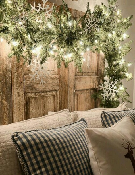 a lit up evergreen garland with large snowflakes over the sofa is a great way to accent your sitting space