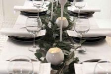 13 a minimalist Christmas tablescape with an evergreen and fresh greenery runner, white candleholders and candles, black porcelain
