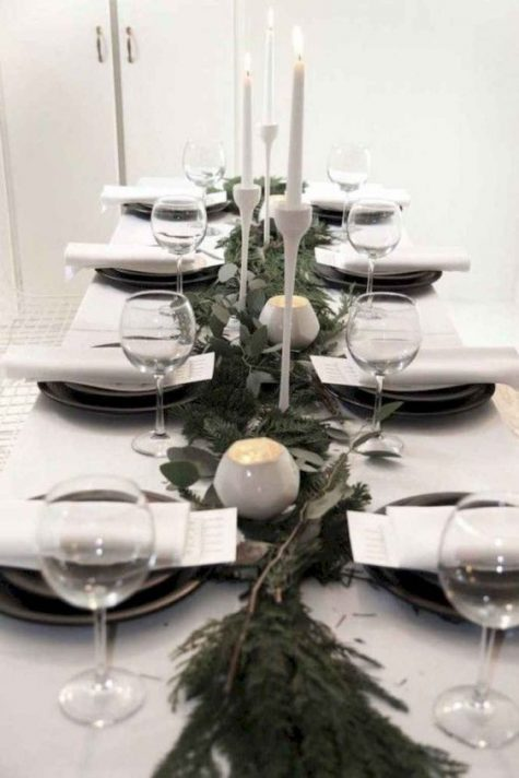 a minimalist Christmas tablescape with an evergreen and fresh greenery runner, white candleholders and candles, black porcelain