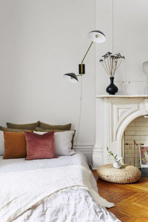 a beautiful Parisian bedroom with a faux fireplace with a gorgeous mantel and some white subway tiles inside