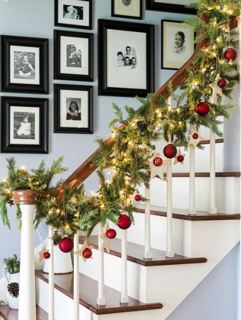 a lit up garland with red ornaments for banister decor is a very pretty and very stylsh idea for holidays