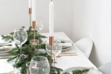 14 a minimalist Christmas tree with an evergreen and snowy pinecone runner, copper cutlery and candleholders, simple linens