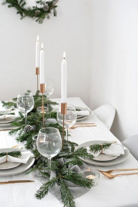 a minimalist Christmas tree with an evergreen and snowy pinecone runner, copper cutlery and candleholders, simple linens