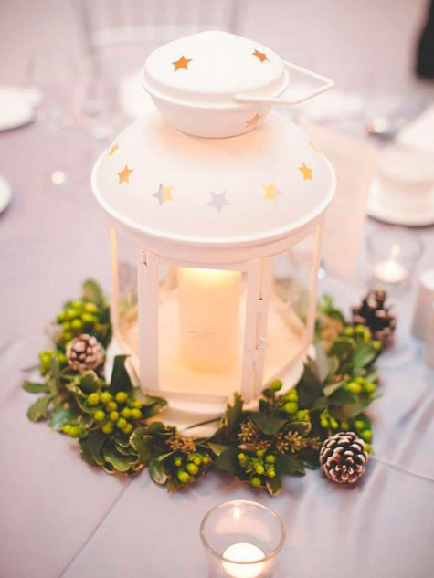a super cozy Christmas centerpiece made of IKEA ROTERA lantern and some evergreens and snowy pinecones can be even used at weddings