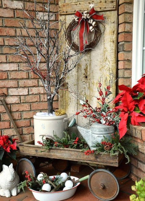 a vintage cart with watering cans, pots and evergreens, a wreath with a red bow and fabric blooms is great for decorating outdoors