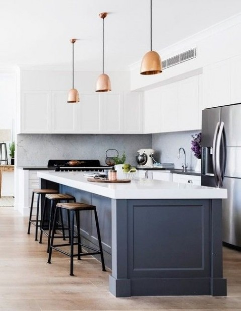 a white kitchen with a navy kitchen island and black and white countertops for more contrast