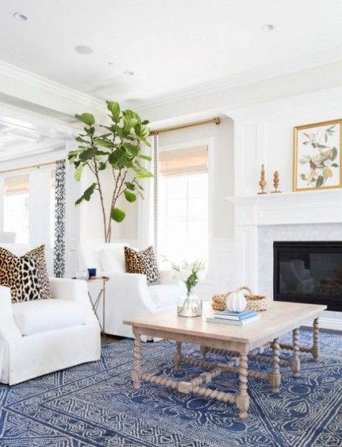 a blue printed rug takes over the neutral coastal room, and leopard printed pillows add interest to it