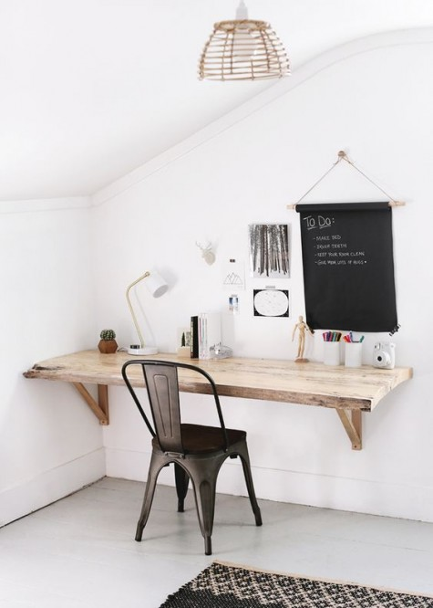 a farmhouse style floating desk in the corner with a metal chair and a chalkboard for making notes make up a cozy nook for work