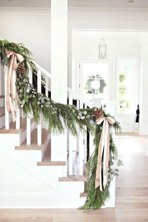 a lush evergreen garland with eucalyptus, pinecones and striped ribbon bows is a nice farmhouse-like decoration
