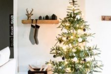 15 a minimalist Christmas tree with lights and black and white ornaments plus a plaid skirt is very chic and minimal