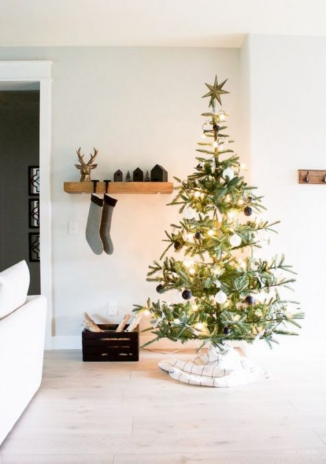 a minimalist Christmas tree with lights and black and white ornaments plus a plaid skirt is very chic and minimal