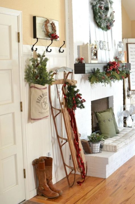 a vintage Christmas entryway with a sleigh, red bells, evergreens and red berries, pillows and pinecones