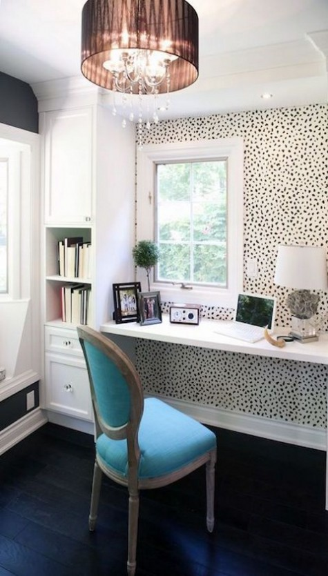 a floating desk by the window and some storage units plus Dolmatin print wallpaper and a blue chair for a quirky touch