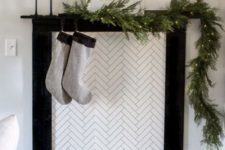 16 a minimalist faux fireplace with candles, simple grey stockings and an evergreen garland with lights