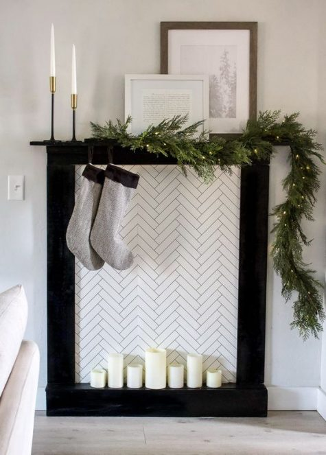 a minimalist faux fireplace with candles, simple grey stockings and an evergreen garland with lights