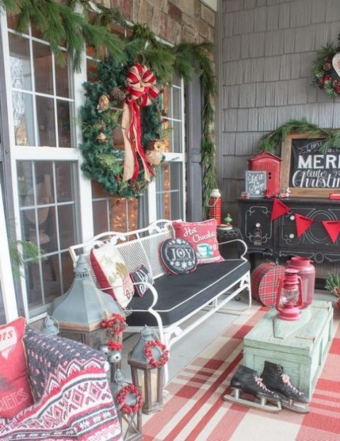 a vintage Christmas porch in red, white and black with comfy furniture and colorful pillows, skates, an evergreen wreath and evergreens all around