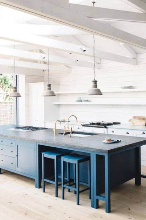 an oversized kitchen island in blue is a great idea to add color to such a pure white space, and dark grey countertop creates even more contrast