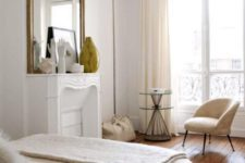 17 a chic neutral Parisian bedroom with a faux fireplace, a statement mirror, a neutral chair and a large bed