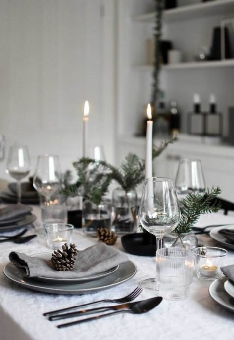 a modern Nordic Christmas table with grey plates, candles, evergreens and pinecones is all-natural and welcoming