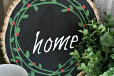 17 a painted Christmas sign with chalkboard paint, bright green and red decor and a chalk word for a cozy rustic feel