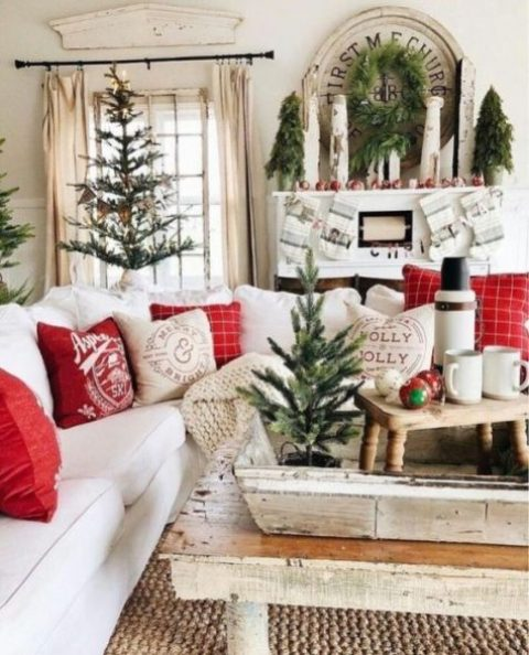 a vintage farmhouse Christmas living room with mini trees, red ornaments, red and white pillows and stockings