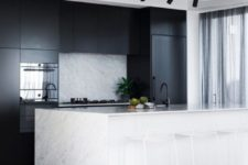 17 sleek black cabinets and a white kitchen island with a stone countertop and a matching backsplash