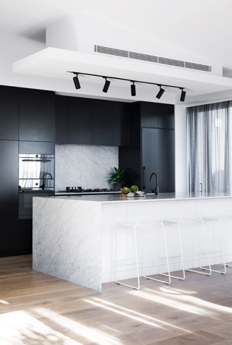sleek black cabinets and a white kitchen island with a stone countertop and a matching backsplash