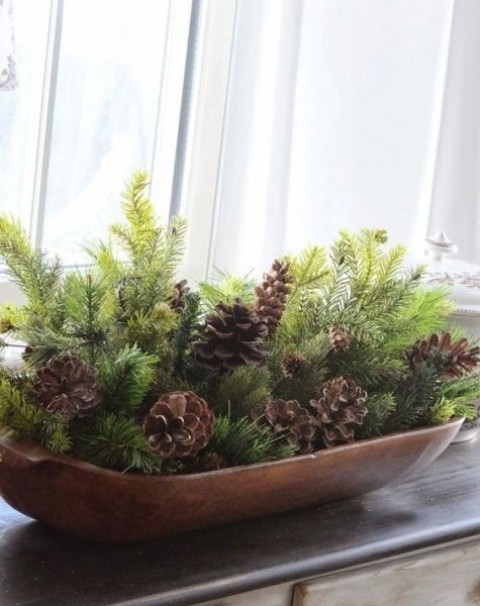 a bread bowl with evergreens and pinecones is a stylish Christmas centerpiece that inspires