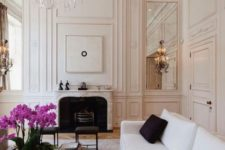 18 a gorgeous and refined Parisian living room with molding, mirrors, a statement chandelier, a white sofa with black pillows and a fireplace