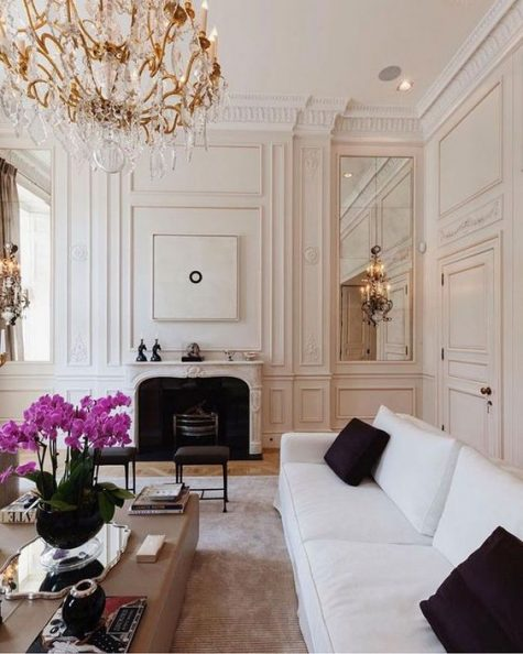 a gorgeous and refined Parisian living room with molding, mirrors, a statement chandelier, a white sofa with black pillows and a fireplace