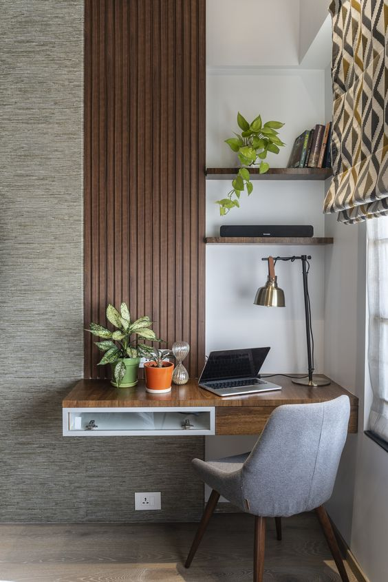 a little work nook with a floating desk with open and closed storage, a couple of shelves, a table lamp and printed curtains that match