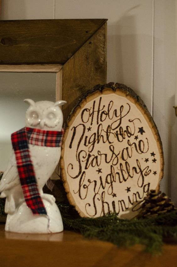 a rough wood slice Christmas sign with woodburnt words looks chic and cozy and can be used for rustic decor