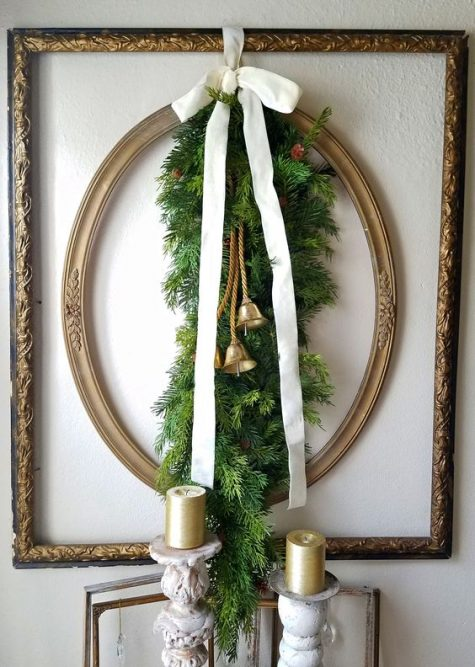 a vintage refined and at the same time rustic Christmas decoration of frames, evergreens, a white ribbon bow and bells plus gold candles