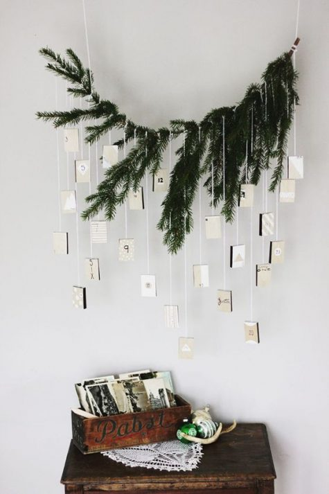 an evergreen advent calendar with boxes hanging down from it for a minimalist space with a natural feel
