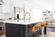 18 white cabinets and a black kitchen island with the same white countertops, plywood chairs and gold touches for warm touch