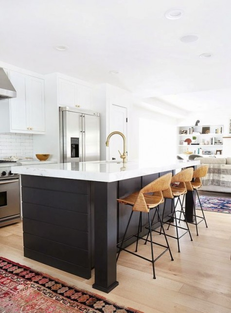white cabinets and a black kitchen island with the same white countertops, plywood chairs and gold touches for warm touch