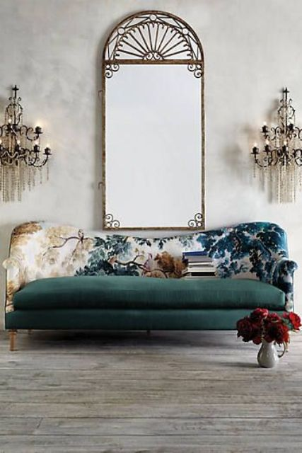 a bold sofa with a dark green seat and a bold printed back with botanical patterns and contrasting colors is chic