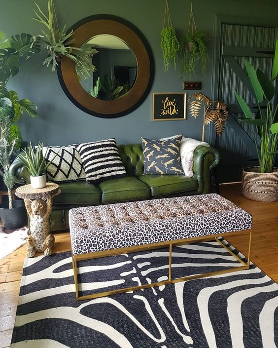 a dramatic zebra rug is the main statement piece here, and an animal print ottoman and pillows are additional ones