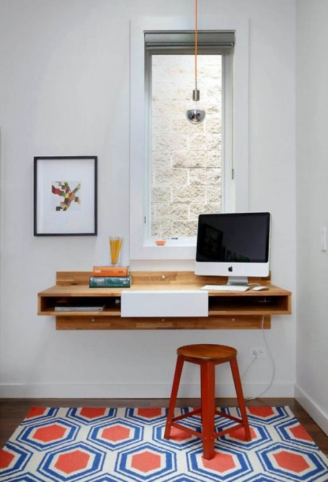a mid-century modern nook with a floating desk by the window with storage space and a stool plus a bulb