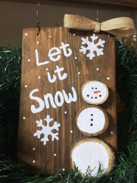 a simple wooden sign with a wood slice snowman is a cute decoration that can be DIYed by your kids