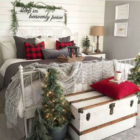 a vintage rustic Christmas bedroom with mini lit up trees, crochet blankets and plaid pillows, evergreens