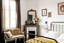20 a beautiful Parisian bedroom with printed curtains, a crystal chandelier, a retro metal bed, a chic mustard loveseat and a marble clad fireplace
