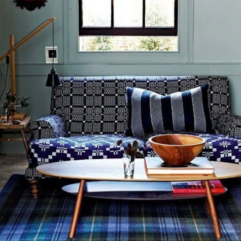 a bold sofa with a windowpane printed back and armrests and a geometric print seat fits this moody interior making it brighter