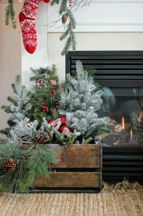a crate arrangement with evergreens, red ornaments, pinecones is a cozy and fresh decor idea  for holidays